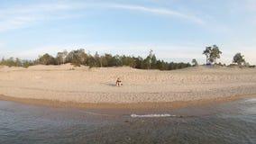 Il fuco sorvola l'acqua verso la fucilazione della riva una ragazza che si siede sul disegno della spiaggia stock footage