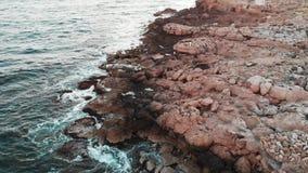 Il fuco vola lungo la spiaggia con la spiaggia rocciosa Vista aerea di grandi onde che colpiscono le pietre dell'oceano stock footage