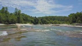 Il fuco vola vicino al fiume basso con le rapide fra i tropici