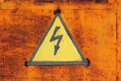 Il fulmine ad alta tensione firma dentro il triangolo giallo sulla porta arrugginita del metallo, fondo astratto di lerciume Fotografia Stock