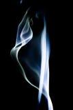 Il fumo blu astratto turbina sopra fondo nero Immagine Stock