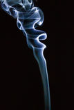 Il fumo blu astratto turbina sopra fondo nero Fotografie Stock