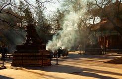 Il fumo dagli ospiti brucia l'incenso dalle statue cinesi in tempio di Yonghegong, Lama Temple del leone del guardiano, a Pechino fotografie stock