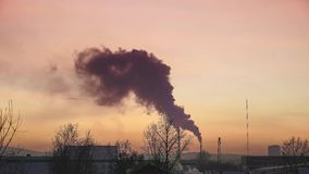 Il fumo dai tubi delle caldaie e dalle case nell'inverno contro il cielo di tramonto, tracce di aerei di volo nel cielo stock footage