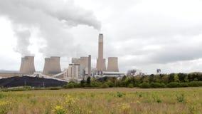 Il fumo della centrale atomica aumenta dalle costruzioni annerite di un sito industriale stock footage