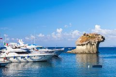 Il Fungo. Natural mushroom shaped rock. Lacco Ameno, Italy - August 17, 2015: Yachts with passengers on board moored near Il Fungo. Natural landmark, mushroom Stock Photography
