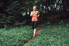 Il funzionamento caucasico della donna sullo sport d'uso della traccia della foresta copre immagini stock