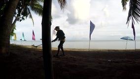 Il funzionamento della giovane donna come rastrellamento del pulitore della spiaggia sporca, detriti sulla spiaggia sabbiosa trop stock footage