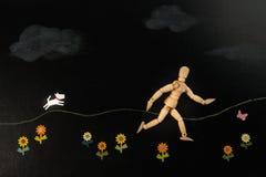 Il funzionamento di modello umano di legno con la carta bianca del cane ha tagliato in giardino floreale fotografia stock