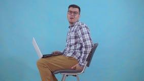 Il funzionamento di seduta dell'uomo su un computer portatile sta avvertendo il dolore ed il disagio dagli emorroidi si chiude su archivi video
