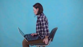 Il funzionamento di seduta della donna su un computer portatile sta avvertendo il dolore ed il disagio dagli emorroidi archivi video