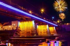 Il fuoco d'artificio sopra la città di notte del ponte ha riflesso in acqua Uzhorod immagini stock