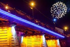 Il fuoco d'artificio sopra la città di notte del ponte ha riflesso in acqua Uzhorod fotografia stock libera da diritti