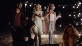 Il fuoco di accampamento, amici riposa con le bevande e le salsiccie sugli spiedi su fondo delle lampade di ardore nella sera tir