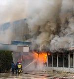 Il fuoco ed il forte fumo hanno coperto la costruzione Immagine Stock