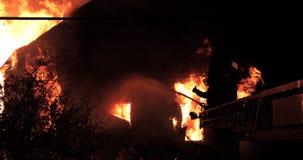 Il fuoco enorme che ardono in fuoco della casa ed il pompiere spruzzano l'acqua con il tubo flessibile in ombra video d archivio