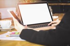 Il fuoco molle della mano della donna che lavorano con il telefono ed il computer portatile sullo scrittorio di legno in ufficio  Fotografie Stock