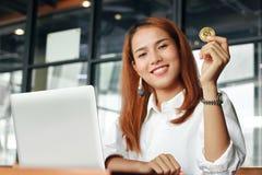 Il fuoco selettivo sulla moneta dorata del bitcoin di cryptocurrency è a disposizione ` tenuto s della donna di affari Soldi virt immagine stock libera da diritti