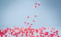 Il fuoco selettivo sulla pillola bianca rosa della capsula cade alla tavola bianca Uso della droga antibiotica con ragionevole Dr immagine stock