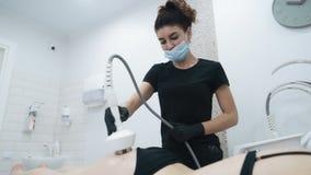 Il fuoco sull'estetista fa la procedura delle anti-celluliti sulle natiche del paziente, movimento lento video d archivio