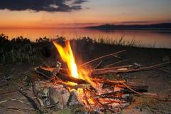 Il fuoco sulla sponda del fiume al tramonto Immagini Stock Libere da Diritti
