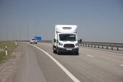 Il furgone bianco guida rapidamente lungo la strada principale fotografia stock