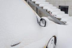 Il furgone giallo compatto congelato dell'automobile ha coperto la neve al giorno di inverno Scena urbana di vita di città nell'i fotografie stock
