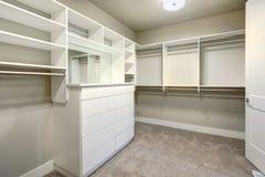 Il gabinetto delle persone senza appuntamento bianco con gli scaffali, i cassetti e le rotaie dei vestiti fotografie stock libere da diritti