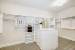 Il gabinetto delle persone senza appuntamento enorme con gli scaffali, i cassetti e le rotaie dei vestiti immagine stock