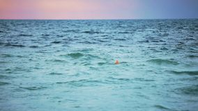 Il galleggiante arancio della boa galleggia nel mare annuvolamento archivi video