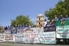 Il galleggiante di una squadra di baseball della piccola lega con le pubblicità del garante fa la sua via principale di modo giù  Fotografie Stock Libere da Diritti