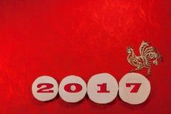 Il gallo dorato e la data rossa 2017 sulla sega dell'ontano hanno tagliato su favoloso decorato rosso Fotografie Stock