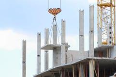 Il gancio della gru alza il grande pannello concreto per costruzione Fotografie Stock Libere da Diritti