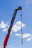 Il gancio della gru con la catena sta appendendo sopra il cantiere Fotografia Stock Libera da Diritti