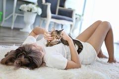 Il gatto nell'abbraccio della donna che si trova sul tappeto della lana Giovane femmina che si trova a letto e che tiene il suo b fotografia stock libera da diritti