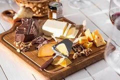 Il genere differente di formaggio e di noci su fondo di legno fotografia stock