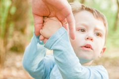Il genitore che tiene la mano del ` s del bambino con un fondo felice fotografie stock libere da diritti