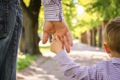 Il genitore che tiene la mano del ` s del bambino con un fondo felice immagine stock