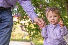 Il genitore che tiene la mano del ` s del bambino con un fondo felice immagine stock libera da diritti