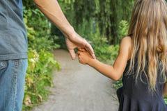 Il genitore che tiene la mano del ` s del bambino con un fondo felice fotografie stock