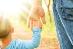Il genitore che tiene la mano del ` s del bambino con un fondo felice immagini stock