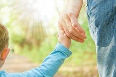 Il genitore che tiene la mano del ` s del bambino con un fondo felice immagini stock libere da diritti