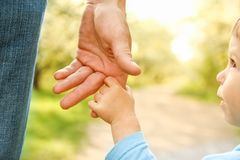 Il genitore che tiene la mano del ` s del bambino con un fondo felice fotografia stock libera da diritti