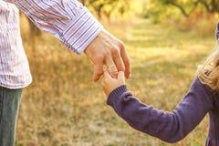 Il genitore che tiene la mano del ` s del bambino con un fondo felice fotografia stock