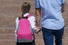 Il genitore conduce dalla mano alla scuola, vista del ` s della figlia del primo piano da dietro immagine stock libera da diritti