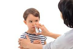 Il genitore di una ragazza applica uno spray nasale Fotografie Stock