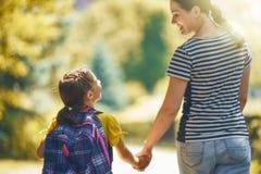 Il genitore e l'allievo vanno a scuola immagine stock