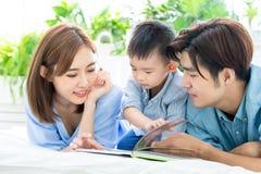 Il genitore ha letto il libro con il bambino immagine stock libera da diritti