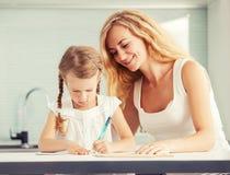 Il genitore insegna ad un bambino a scrivere fotografie stock