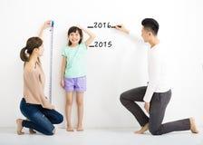 il genitore misura la crescita della figlia fotografia stock libera da diritti